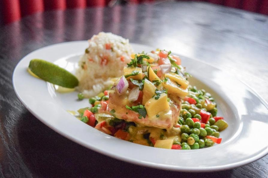salmon fillet with mango-butter sauce, topped with mango pico de gallo, and served with rice and vegetables