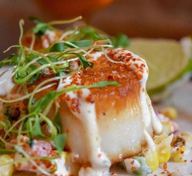 chile-lime dusted seared scallops with corn esquites, queso fresco, micro cilantro, and lime wedge